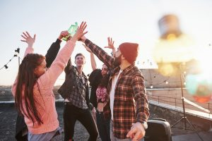 group of friends raised their hands up with alcohol