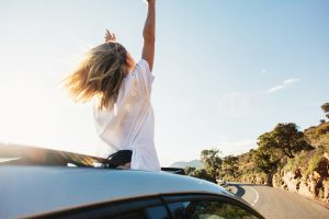 woman in car waving out at the window