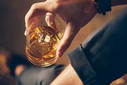 hands holding a glass of whiskey