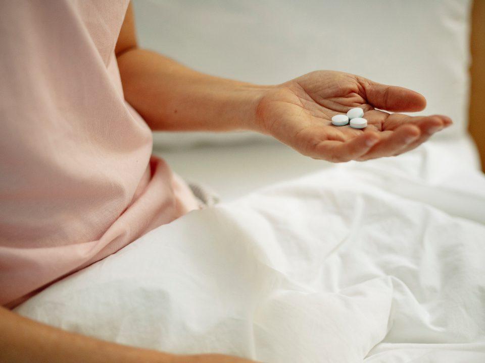 hand holding a drug tablet